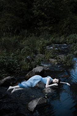 Dorota Gorecka Young woman lying on rock by river