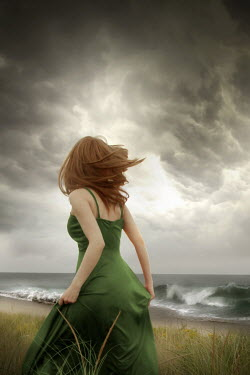 ILINA SIMEONOVA Young woman in green dress standing on beach