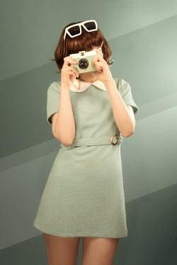 ILINA SIMEONOVA 1960s young woman in green dress with camera