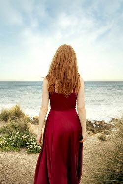 ILINA SIMEONOVA Young woman in red dress standing on beach