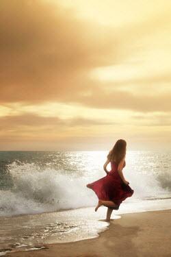 ILINA SIMEONOVA Young woman in red dress running on beach at sunset