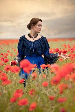 Jaroslaw Blaminsky Young woman in Victorian dress in poppy field