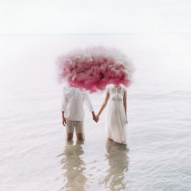 Jovana Rikalo Young couple holding hands in lake with pink cloud