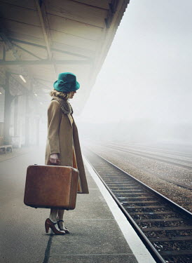 Mark Owen 1940s young woman with suitcase waiting at train station in fog