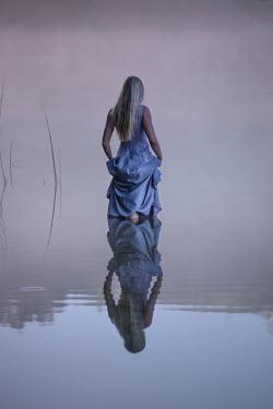 Terry Bidgood Young woman in dress wading in lake