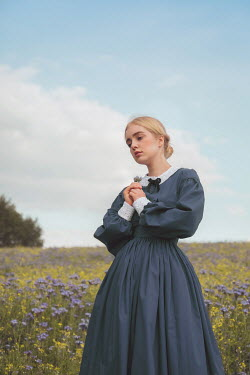 Joanna Czogala Young woman in blue Victorian dress standing in field