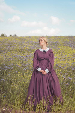 Joanna Czogala Young woman in pink Victorian dress standing in field