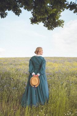 Joanna Czogala Young woman in green Victorian dress standing in field