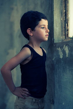 Mohamad Itani Boy in tank top by window of abandoned house