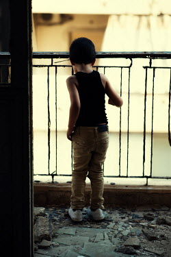 Mohamad Itani Boy in black tank top on balcony of abandoned house