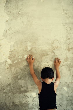 Mohamad Itani Boy leaning on wall of abandoned house