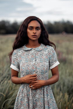 Rekha Garton Young woman in vintage dress in field