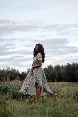 Rekha Garton Young woman in vintage floral dress in field