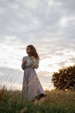 Rekha Garton Young woman in vintage dress at sunset