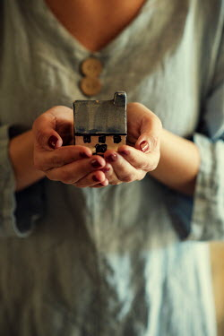 Mohamad Itani Hands of young woman holding toy house