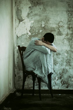Mohamad Itani Young woman crying on chair in abandoned house
