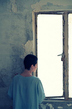 Mohamad Itani Young woman with short hair by window in abandoned house