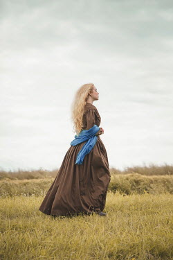 Joanna Czogala Young woman in brown Victorian dress in field
