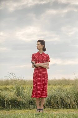 Joanna Czogala Young woman in red 1940s dress standing in field