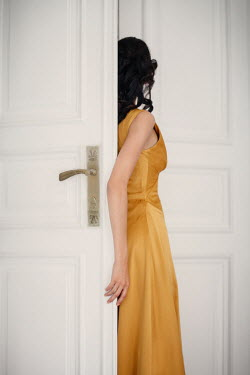 Nikaa Young woman in yellow dress in doorway
