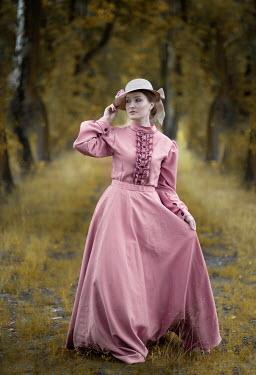 Jaroslaw Blaminsky Victorian woman in pink dress walking under trees