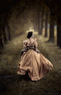 Jaroslaw Blaminsky Young woman in Victorian dress walking under trees