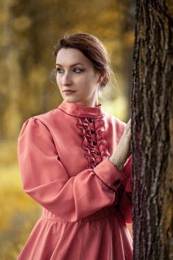 Jaroslaw Blaminsky Victorian woman with pink dress by tree trunk