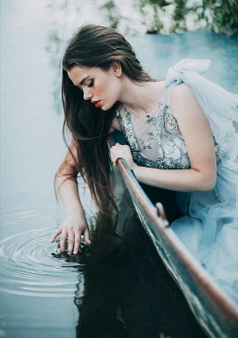 Jovana Rikalo Young woman touching water from boat on lake
