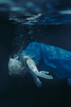 Magdalena Russocka woman in blue dress floating underwater