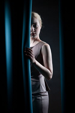 Magdalena Russocka elegant woman behind curtains
