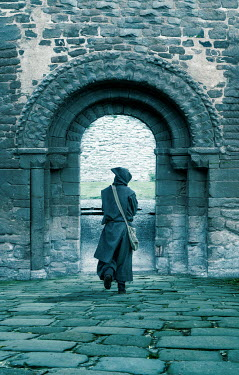 Stephen Mulcahey Monk walking under archway