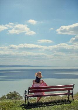 Nikaa WOMAN IN HAT SITTING WATCHING OCEAN Women