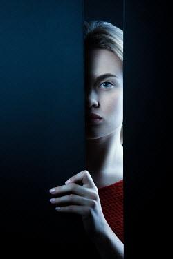 Magdalena Russocka woman staring throught gap in wall