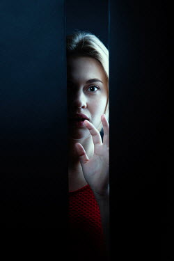 Magdalena Russocka scared woman staring through gap in wall