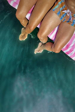 Paolo Martinez TANNED COUPLE SITTING WITH FEET IN WATER Couples