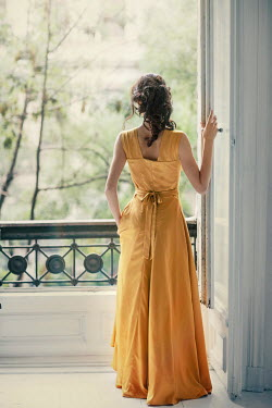 Nikaa BRUNETTE WOMAN IN YELLOW DRESS WATCHING BY BALCONY Women