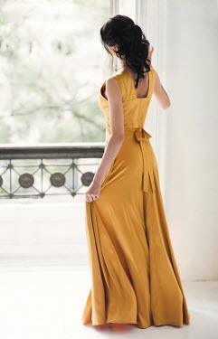 Nikaa BRUNETTE WOMAN IN YELLOW DRESS WATCHING AT WINDOW Women