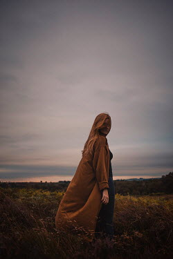 Shelley Richmond WOMAN IN BROWN COAT IN COUNTRYSIDE AT DUSK Women