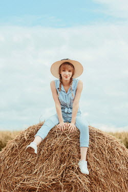 Tijana Moraca GIRL IN JEANS AND STRAW HAT SITTING ON HAY BALE Women