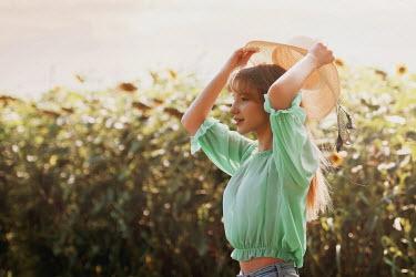 Tijana Moraca GIRL HOLDING STRAW HAT IN SUNFLOWER FIELD Women