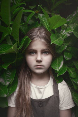 Anna Buczek LITTLE GIRL STANDING IN BUSH WITH LARGE LEAVES Children