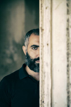 Mohamad Itani MAN WITH BEARD STANDING IN SHABBY BUILDING Men