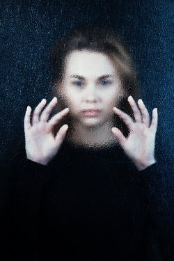 Magdalena Russocka young woman pressing hands behind frosted glass
