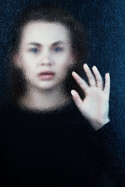 Magdalena Russocka young woman pressing hand behind frosted glass