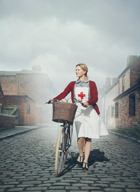 Mark Owen NURSE PUSHING BIKE ON COBBLED STREET Women