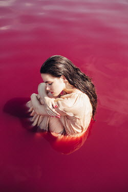 Jovana Rikalo BRUNETTE WOMAN SITTING IN PINK WATER Women