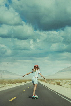Robin Macmillan GIRL SKATEBOARDING ON DESERT ROAD Children