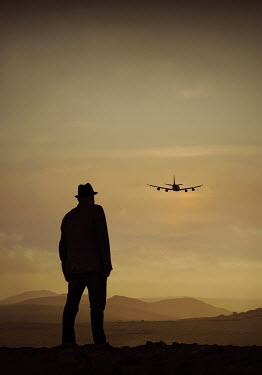 Lyn Randle SILHOUETTED MAN WATCHING AEROPLANE FLYING AT DUSK Men