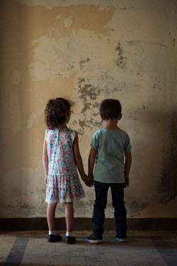 Mohamad Itani LITTLE GIRL AND BOY HOLDING HANDS IN SHABBY ROOM Children