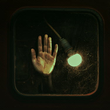 Marko Nadj MALE HAND PRESSING ON WINDOW WITH LIGHT BULB Men